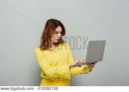 Concentrated Woman In Yellow Blouse Typing On Laptop On Grey.