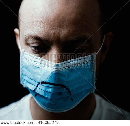 Man Wearing A Face Mask With A Sad Mouth Painted On It. Isolated On Black Background With Shallow De