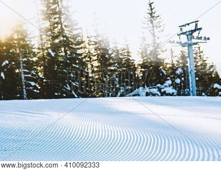 Close Up Of Groomed Tracks On A Slope In A Downhill Ski Resort On A Sunny Day. Shallow Depth Of Fiel