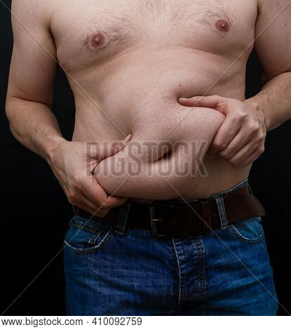 Man With Extra Weight On His Belly Grabs His Skin. Isolated On Black Background.