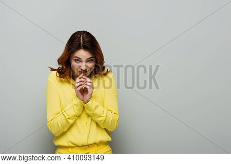 Sly Woman With Curly Hair Smirking While Looking At Camera On Grey.