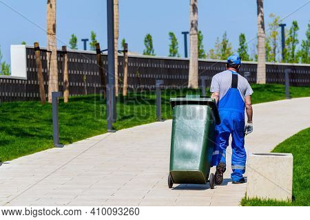 Janitor Rolls Trash Can On Wheels. Cleaning Service In Modern Park.