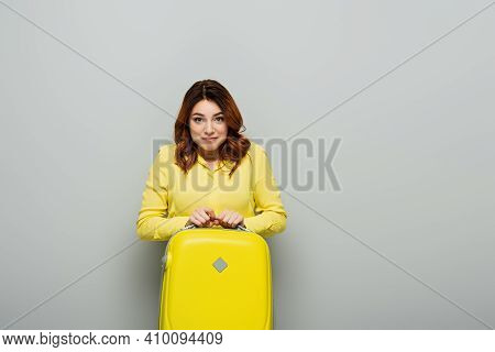 Cheerful Woman In Yellow Blouse Looking At Camera While Standing With Suitcase On Grey.