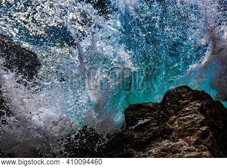 Turquoise Waves Of Sea Water Break And Spray Drops On Stones. Close-up. Red Sea