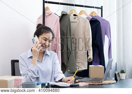 Young Asian women use smartphones to take photos of their clothes and chat with customers to confirm