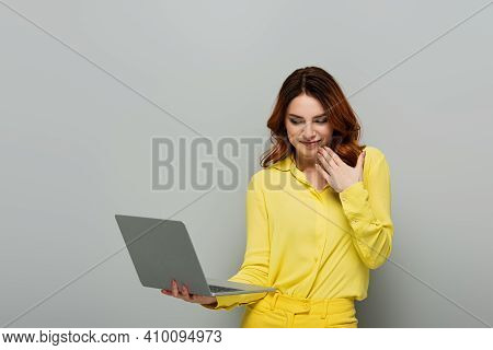Smirking Woman Holding Hand Near Face While Holding Laptop On Grey.