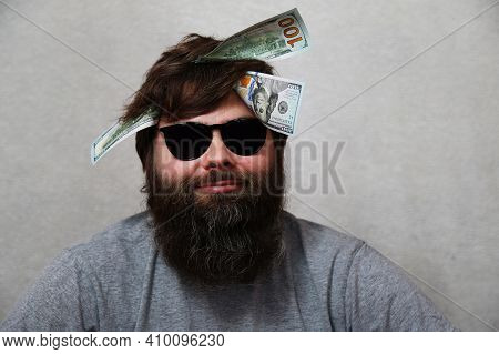 Dollar Bills In The Head Of A Man With A Beard On A Gray Background. Concept: A Man Thinks About Mon