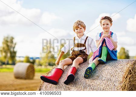 Two Little Kid Boy And Girl In Traditional Bavarian Costumes In Wheat Field. German Children Sitting