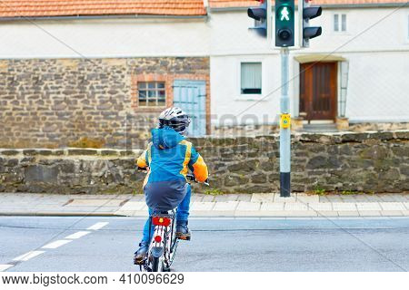 Active Preschool Kid Boy In Helmet Biking On Bicycle In The City. Happy Child In Colorful Clothes An