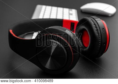 Headphones With Computer Keyboard And Computer Mouse On Black. Close Up.