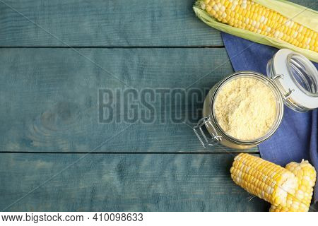 Corn Flour In Glass Jar And Fresh Cobs On Blue Wooden Table, Flat Lay. Space For Text