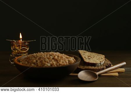 Great Lent Dinner And Burning Candle On Wooden Table