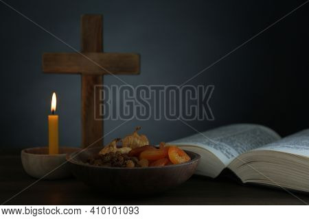 Cross, Bible, Candle And Dried Fruits On Wooden Table, Space For Text. Lent Season