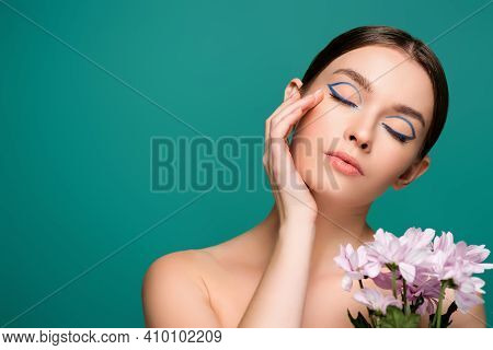 Young Woman With Blue Eyeliner On Closed Eyes Posing Near Pink Chrysanthemums Isolated On Green