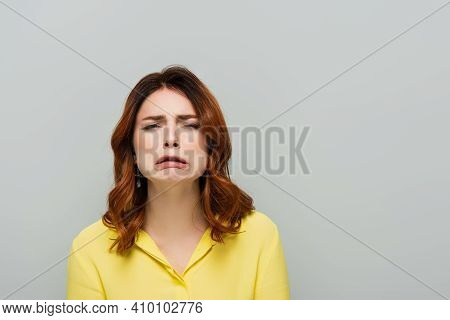 Discouraged Woman Looking At Camera And Grimacing Isolated On Grey.