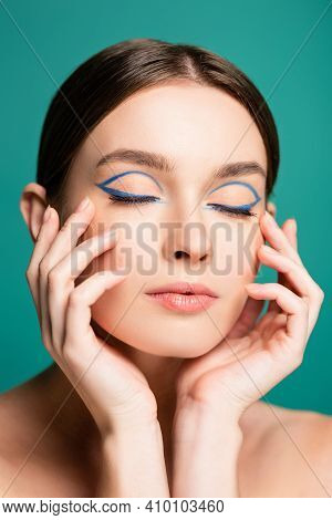 Charming Woman With Blue Eyeliner In Closed Eyes Posing With Hands Near Face Isolated On Green