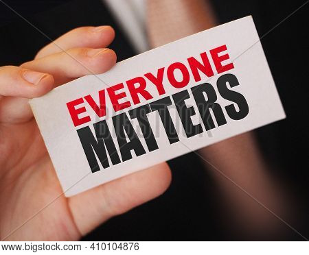 Businessman Holding A Card With Text Everyone Matters. Equality And Diversity Concept.