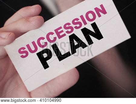 Succession Plan Words On A Card In Hand Of Businessman. Business Profit And Success Concept.