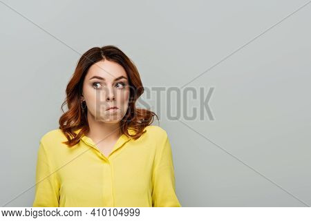 Discouraged Woman With Curly Hair Looking Away Isolated On Grey.