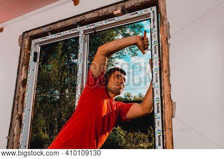 Dolyna, Ukraine July 31, 2020: An Employee Installs A Window Frame, Installing A Plastic Window.