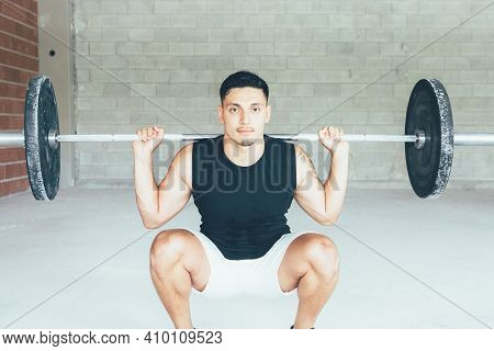 Young Man Doing Barbell Squats Exercises In A Gym. Athletic Man Training His Arms Muscles With Barbe