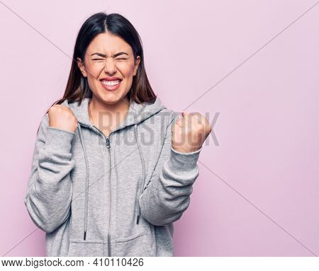 Young beautiful sporty woman wearing sportswear standing over isolated pink background celebrating surprised and amazed for success with arms raised and eyes closed