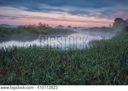 Spring Nature Landscape At Dawn On The Riverside. Misty River In The Morning Against The Colorful Sk