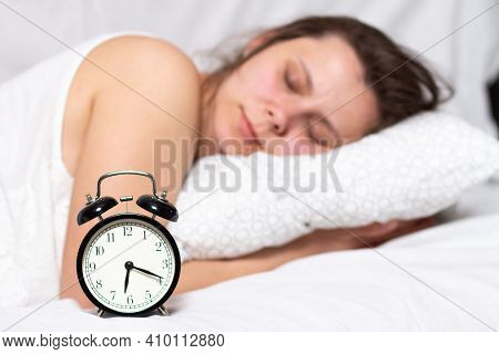 A Young Woman Sleeps In The Bed And Waits For Alarm Clock Call. A Woman Wakes Up In Bed
