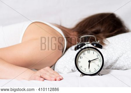 A Young Woman Sleeps In The Bed After Alarm Clock Call In The Morning. The Girl Doesn't Want To Wake
