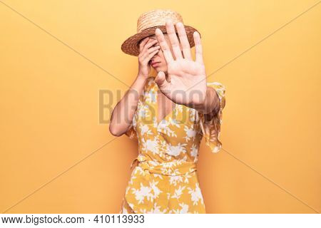 Beautiful blonde woman on vacation wearing summer hat and dress over yellow background covering eyes with hands and doing stop gesture with sad and fear expression. Embarrassed and negative concept.