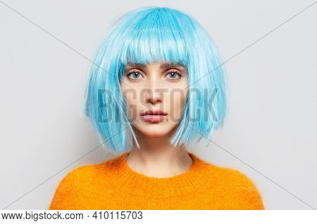 Close-up Studio Portrait Of Confident Young Girl With Blue Bob Hairstyle In Orange Sweater On White