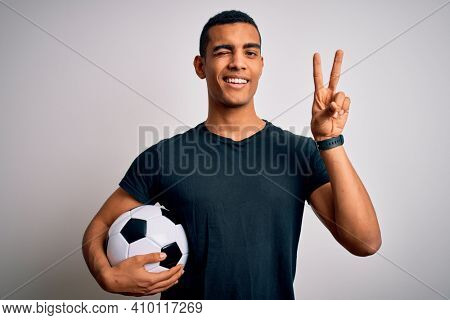 Handsome african american man playing footbal holding soccer ball over white background smiling with happy face winking at the camera doing victory sign with fingers. Number two.
