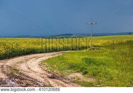 Cross Near Dirty Road Through Spring Rapeseed Yellow Blooming Fields, Cloudy Sky. Natural Seasonal,