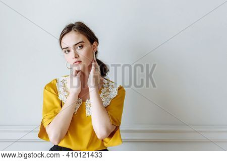 Young Woman In Yellow Blouse On White Wall Background In Studio
