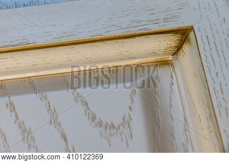 Close-up Corner Of A Textured White Classic Kitchen Facade With Gilding And Imitation Of Fray. Backg