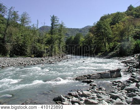 View Of The Mountain River Mzymta Against The Background Of The Caucasus Mountains