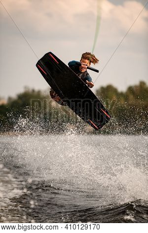 Young Man On Wakeboard Vigorously Jumps And Performs Tricks Over The Water.
