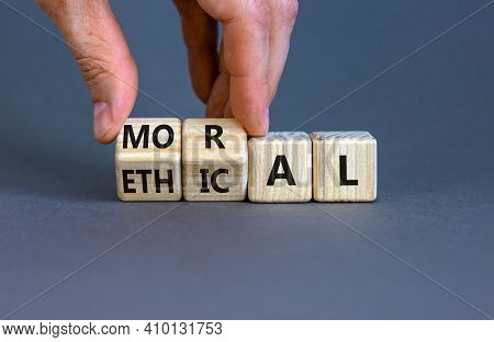 Ethical Or Moral Symbol. Businessman Turns Wooden Cubes And Changes The Word 'moral' To 'ethical' On