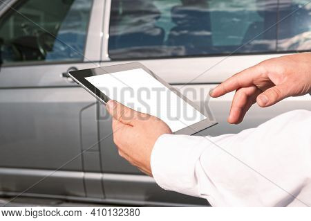 Mock Up Technology. Businessman In A White Shirt Holds A Tablet With A White Screen On The Backgroun