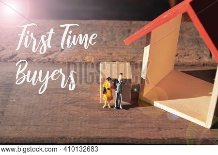 Selective Focus Of People Miniatures And Toy House With Text First Time Buyers.