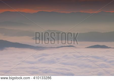 Foggy Above Mountain Againts Colorful Sky