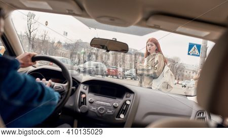 Male Driver Honking The Horn In The Car While Distracted Teenage Girl Using Her Mobile Phone, Crossi