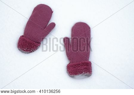 Warm Mittens In The Snow. Two Mittens Lie On White Snow Top View. Cold Season, Snowy Winter.