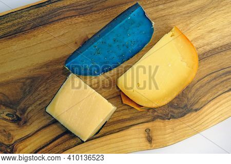 Pieces Of Hard Cheese On A Wooden Board View From Above. Three Pieces Of Different Kinds Of Cheese.