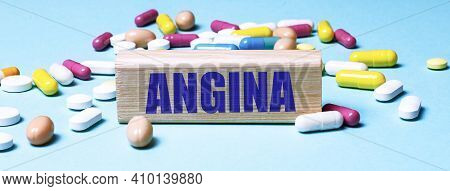A Wooden Block With The Word Angina Stands On A Blue Background Among Multi-colored Pills. Medical C