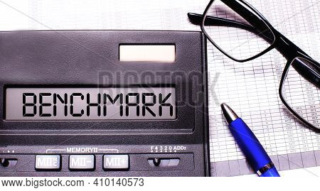 The Word Benchmark Is Written On Wooden Cubes On The Keyboard Next To The Pen.