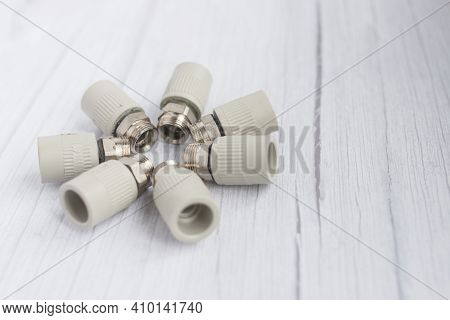 Combined Couplings For Connecting Metal And Polypropylene Water Pipes. Close Up Of Nuts In Circle In