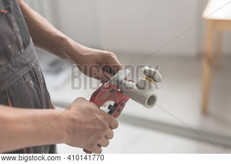 Close-up Of Hand With Red Scissors Cut Pipes For Heating, Or Water Supply. Polypropylene Pipe With T