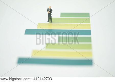 Miniature Businessman Standing On Green Graph And Thinking With Project For Presenting Investment Co