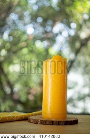 Freshly Orange Smoothie In Tall Glass Put On Wood Table On Garden Background